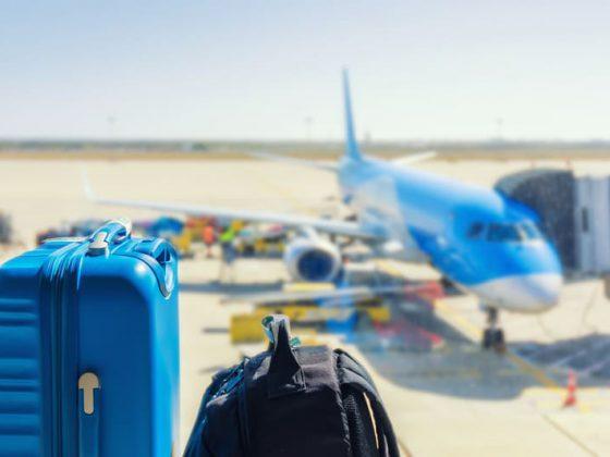Duas malas no detalhe e no fundo um avião na pista de voo
